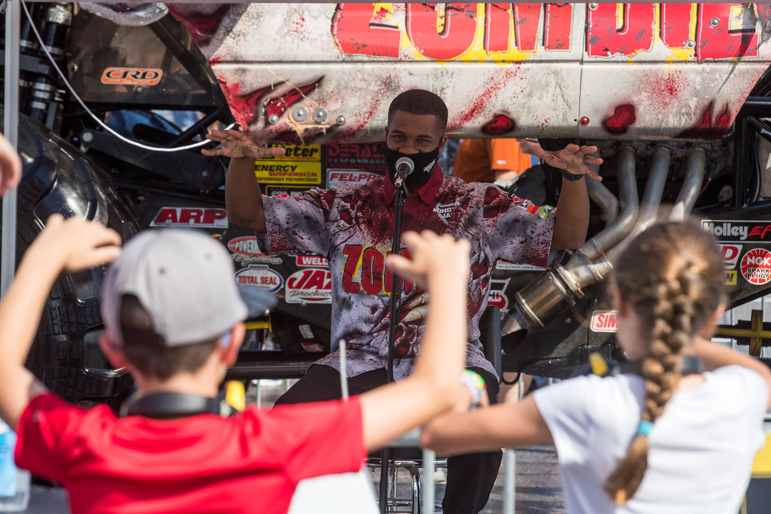 Bari Musawwir, driver of the Zombie truck, throws up the zombie arms with a couple fans during the Monster Jam Pit Party prior to the main event at GEHA Field at Arrowhead on Saturday evening, June 26, 2021.
