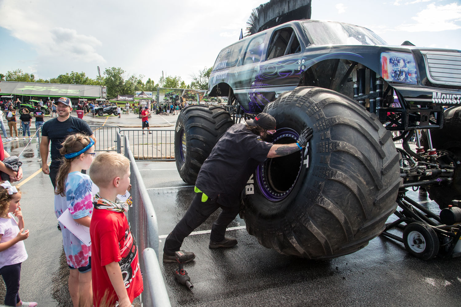 Fans watch as a pit crew demonstrates how to change a tire on the Great Clips Mohawk Warrior truck during the Monster Jam Pit Party prior to the main event at GEHA Field at Arrowhead on Saturday evening, June 26, 2021.