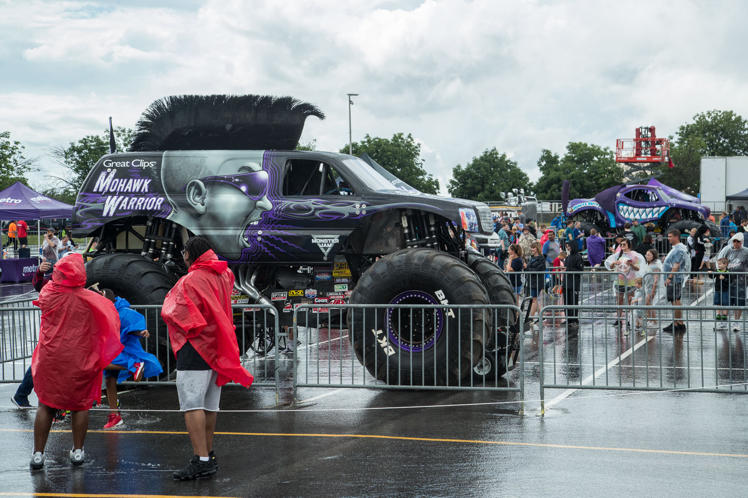 Fans brave the rain while checking out the trucks during the Monster Jam Pit Party prior to the main event at GEHA Field at Arrowhead on Saturday evening, June 26, 2021.